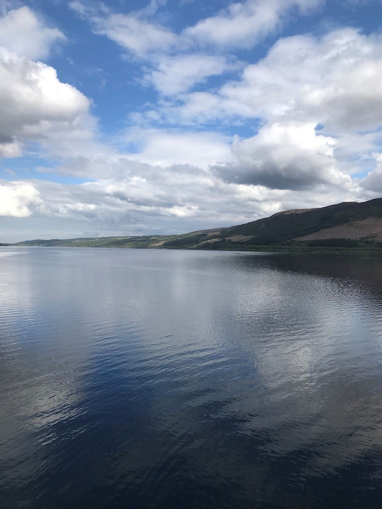 Loch Ness, showing the water, hills and blue sky with clouds