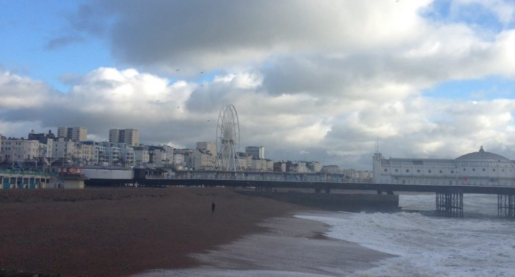 Landscape view of Brighton beach, with sand on the left, water on the right, and Brighton Palace Pier in the distance.