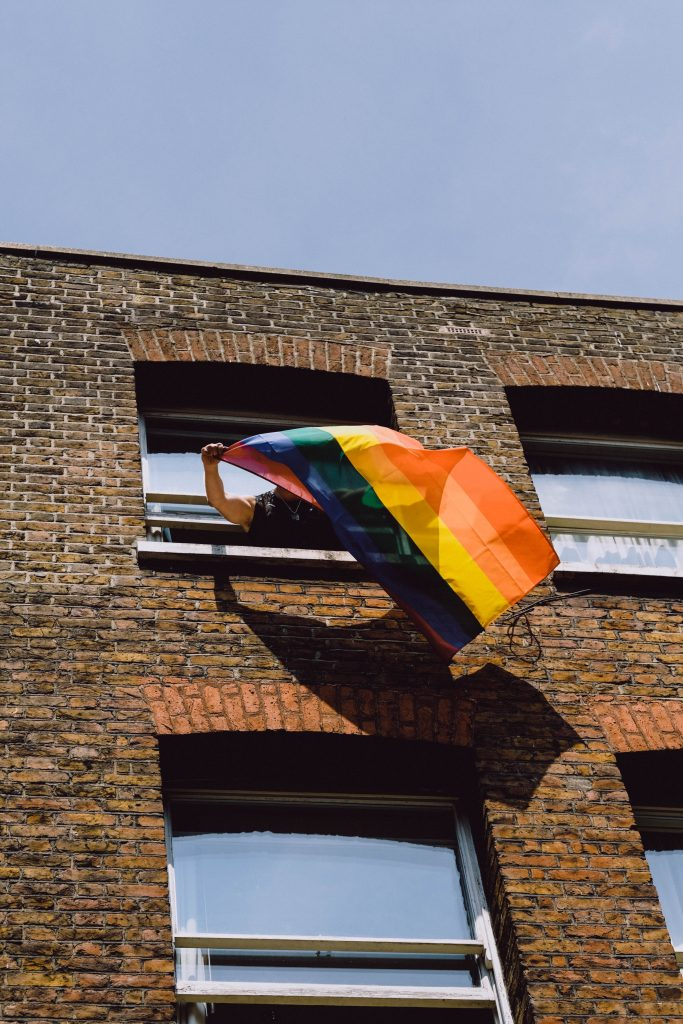 Person holding a rainbow flag out of a window in brick building emphasizing LGBTQ2+ pride in London