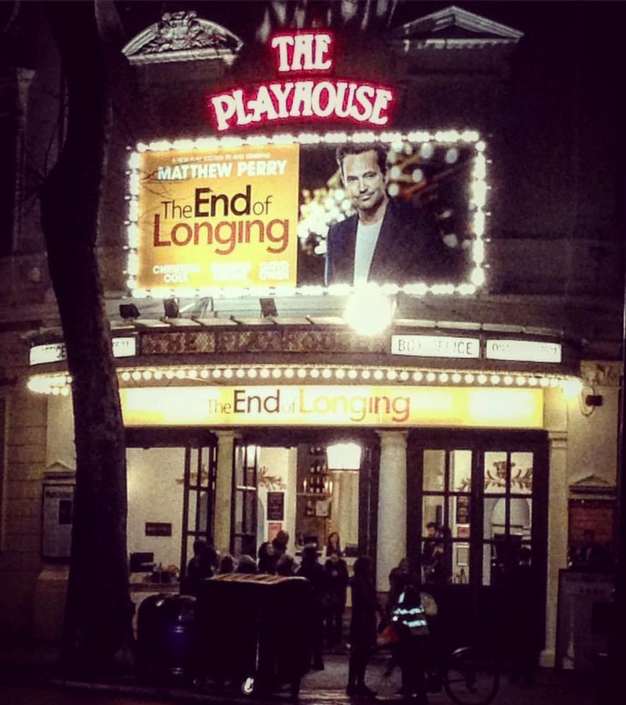 """Lit up theatre facade showing the theatre's name """"The Playhouse"""" and the name of the show, """"The End of Longing"""""""