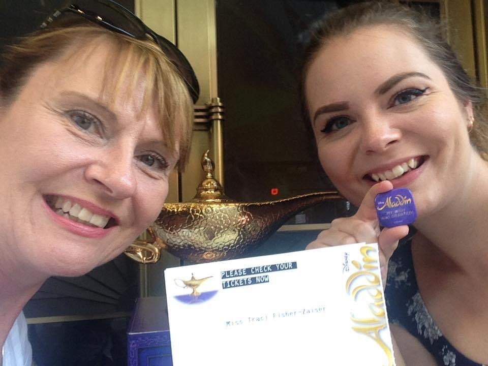 Advisor Brittany (right) and her mom (left) holding up their Aladdin theatre ticket